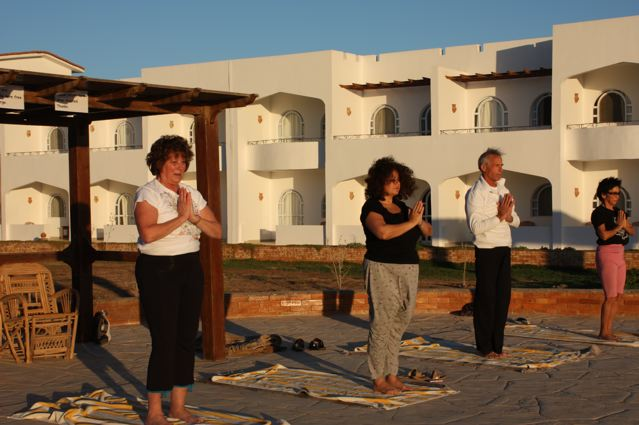 Yoga class at sunrise by the pool