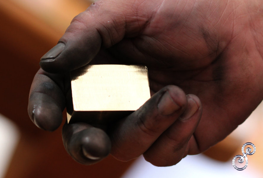 Hand black from polishing holding a gold bar of brass